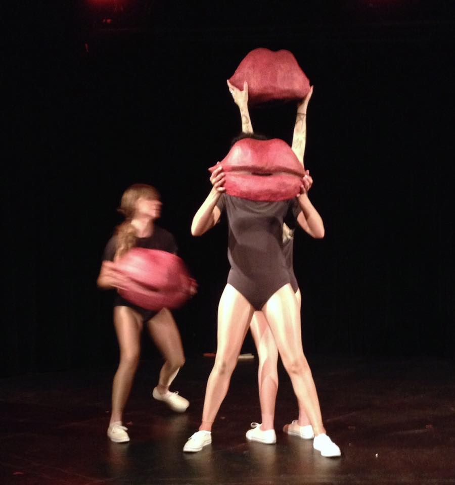 Dancers on stage holding large red lips
