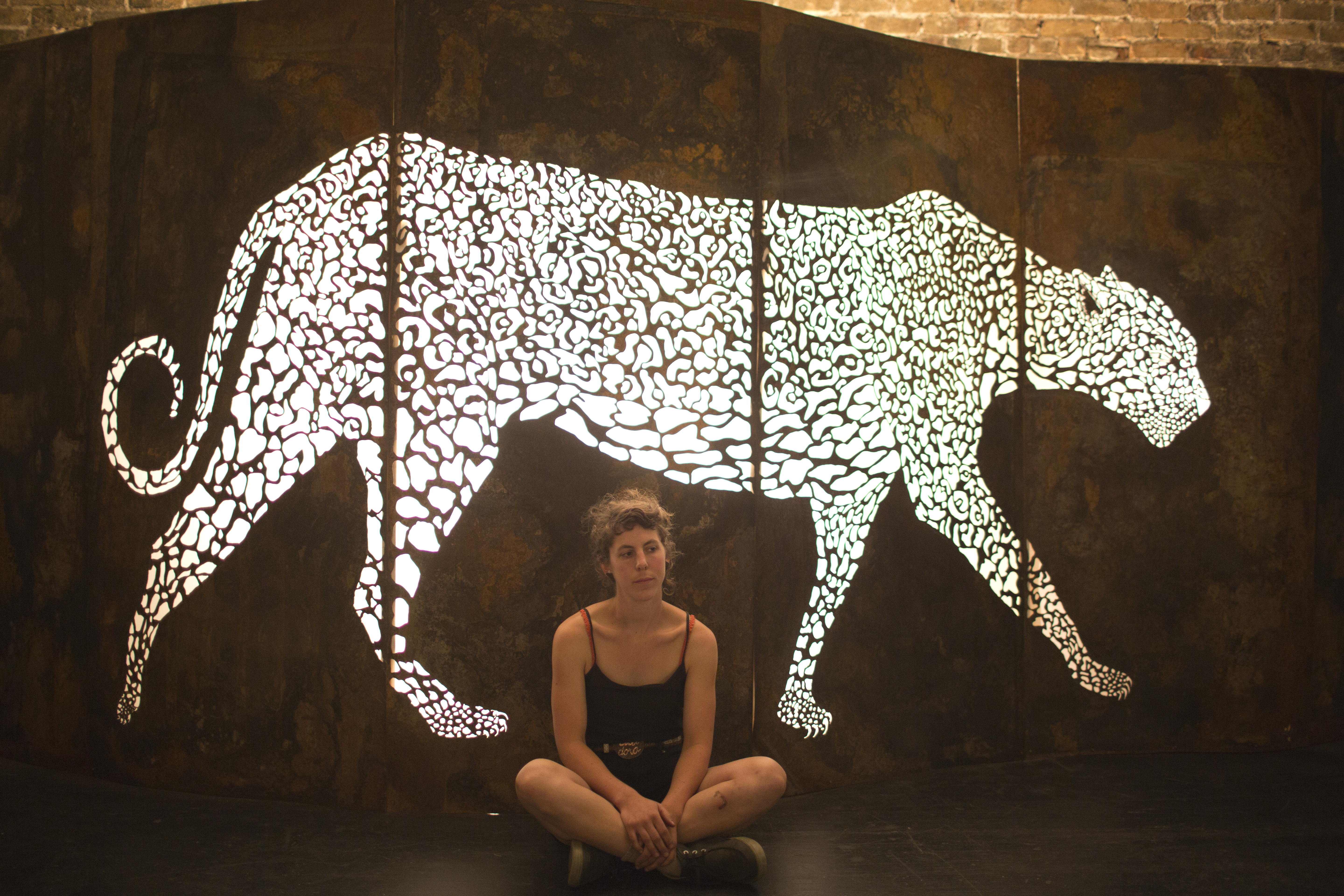 Artist seated in front of an illuminated metal art piece of a leopard