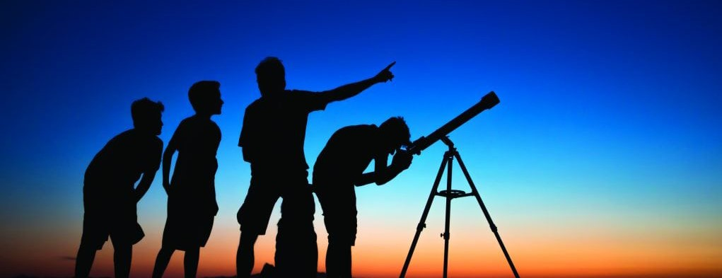 Silhouettes of people looking through a telescope