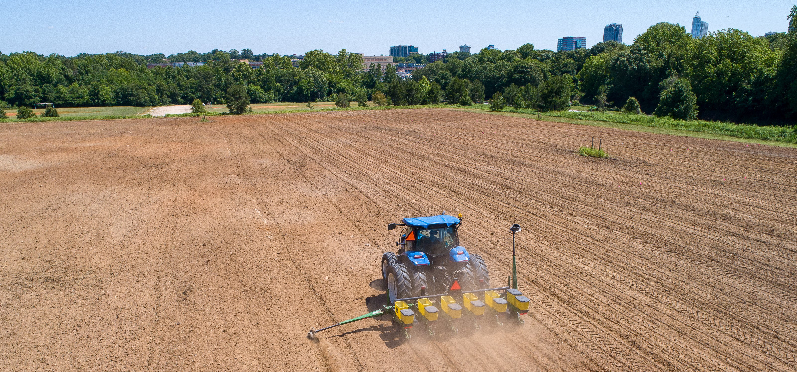 Aerial view of a tractor planting the sunflower field at Dix Park with the city skyline in the distance