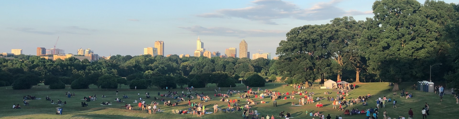 View of Flowers Field at Dix park with people on the lawn and the Raleigh skyline in the background