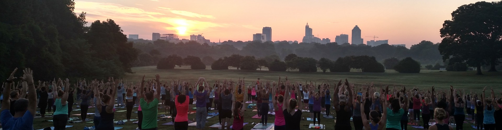 Crowd of people doing yoga in a field at Dix Park with the sun rising in the background