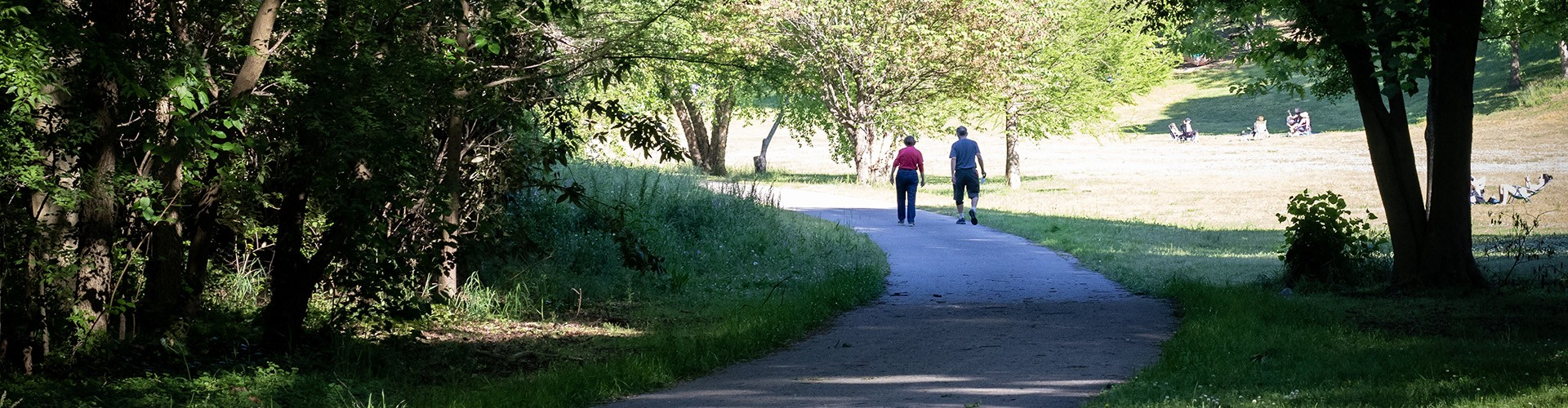 Two people walking on the Rocky Branch Greenway